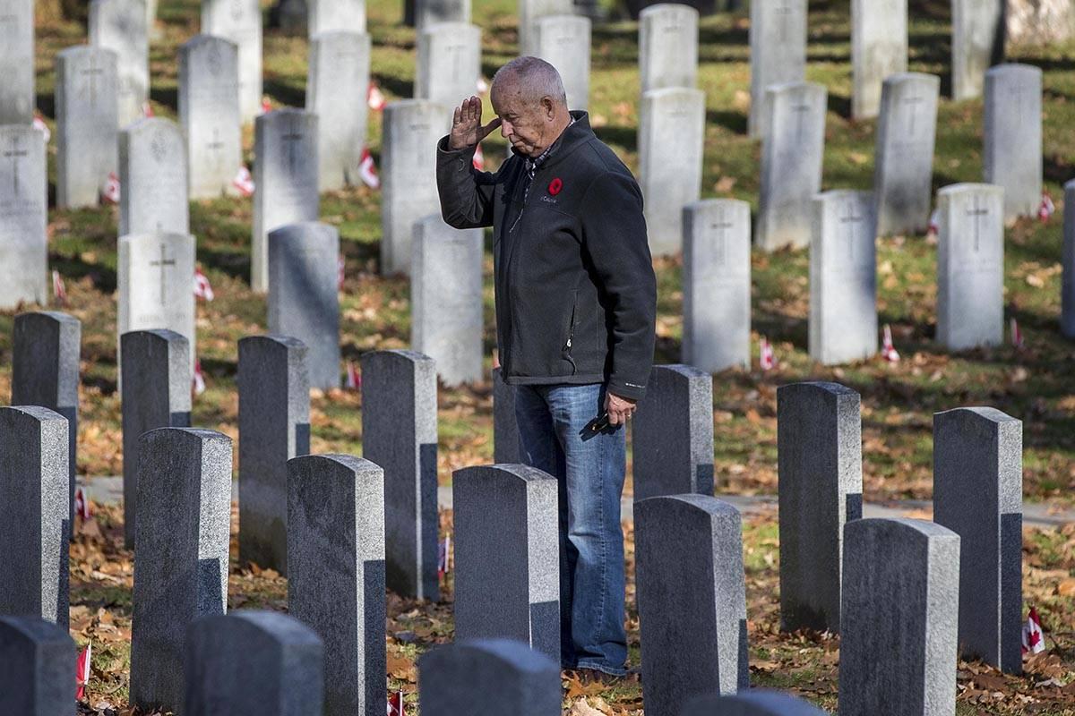 Peter Dawe salutes his son Capt. Matthew Dawe's grave in Kingston, Ont., on Tuesday, Nov. 10, 2020. Capt.Matthew Dawe died in Afghanistan on July 4, 2007. THE CANADIAN PRESS/Lars Hagberg