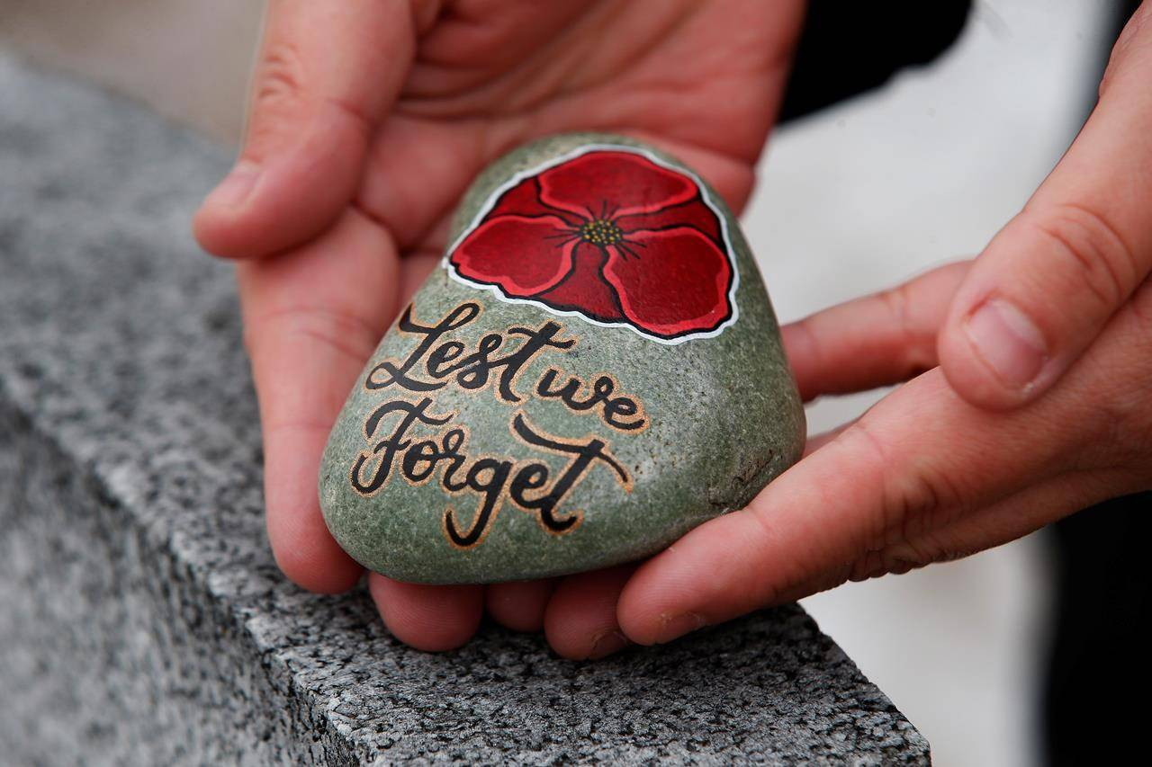 Julie Mungall places her painted stones at the Brookside veterans cemetery in Winnipeg, Saturday, October 24, 2020. Mungall is commemorating Remembrance Day by painting poppies and other designs on rocks and hiding them around the city, sometimes in plain sight, for people to pick up and take home with them. THE CANADIAN PRESS/John Woods