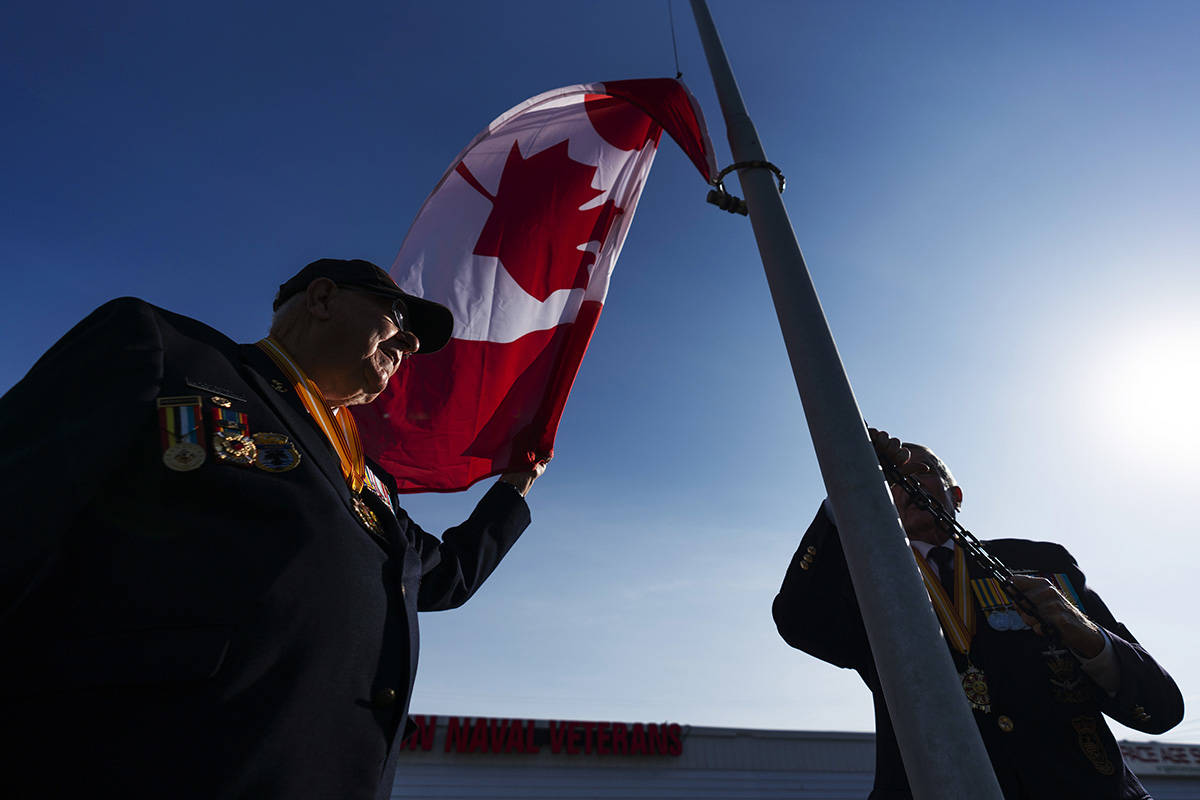 Korean War veterans Andy Barber, left, and Ron Kirk, raise the Canadian flag at the Halton Naval Veterans Association Burlington, Ont. on Friday November 6, 2020. Barber and Kirk served as in the navy as part of a peacekeeping force immediately following the armistice in July 1953. THE CANADIAN PRESS/Mark Blinch