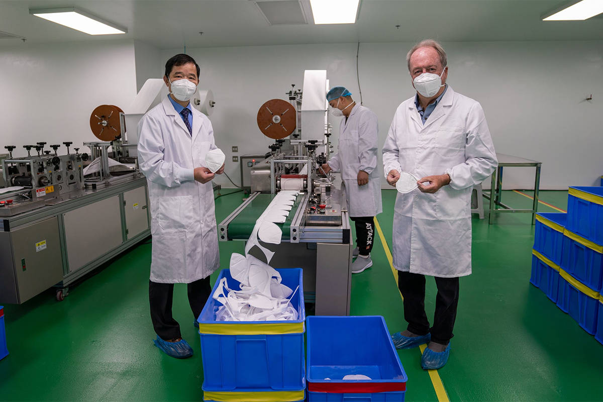 Eternity Medical Equipment co-founder Jeff Wang (left) and Surrey Mayor Doug McCallum stand in Eternity mask production room. (Eternity Medical Equipment photo)