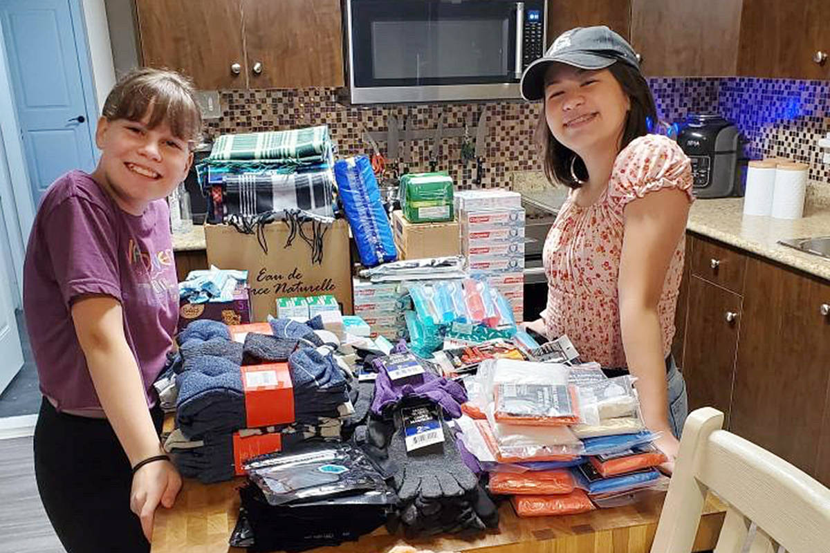 Best friends Payje Burgess (L) and Remy Hinze, with items they collected to help the homeless (special to Langley Advance Times)