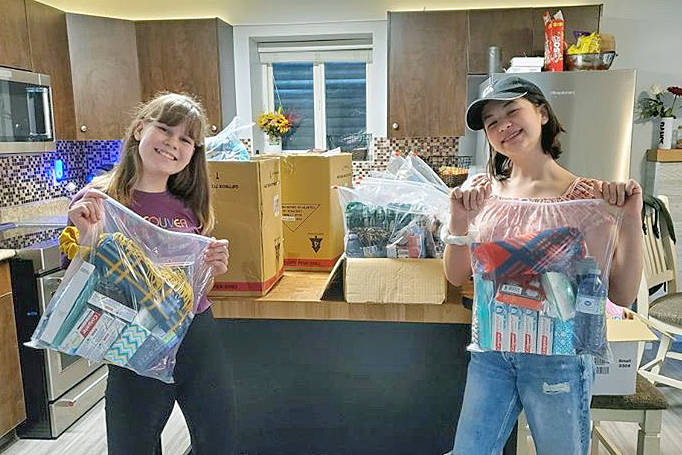 Best friends Payje Burgess (L) and Remy Hinze, with the completed warmup bags they put together to help the homeless (special to Langley Advance Times)