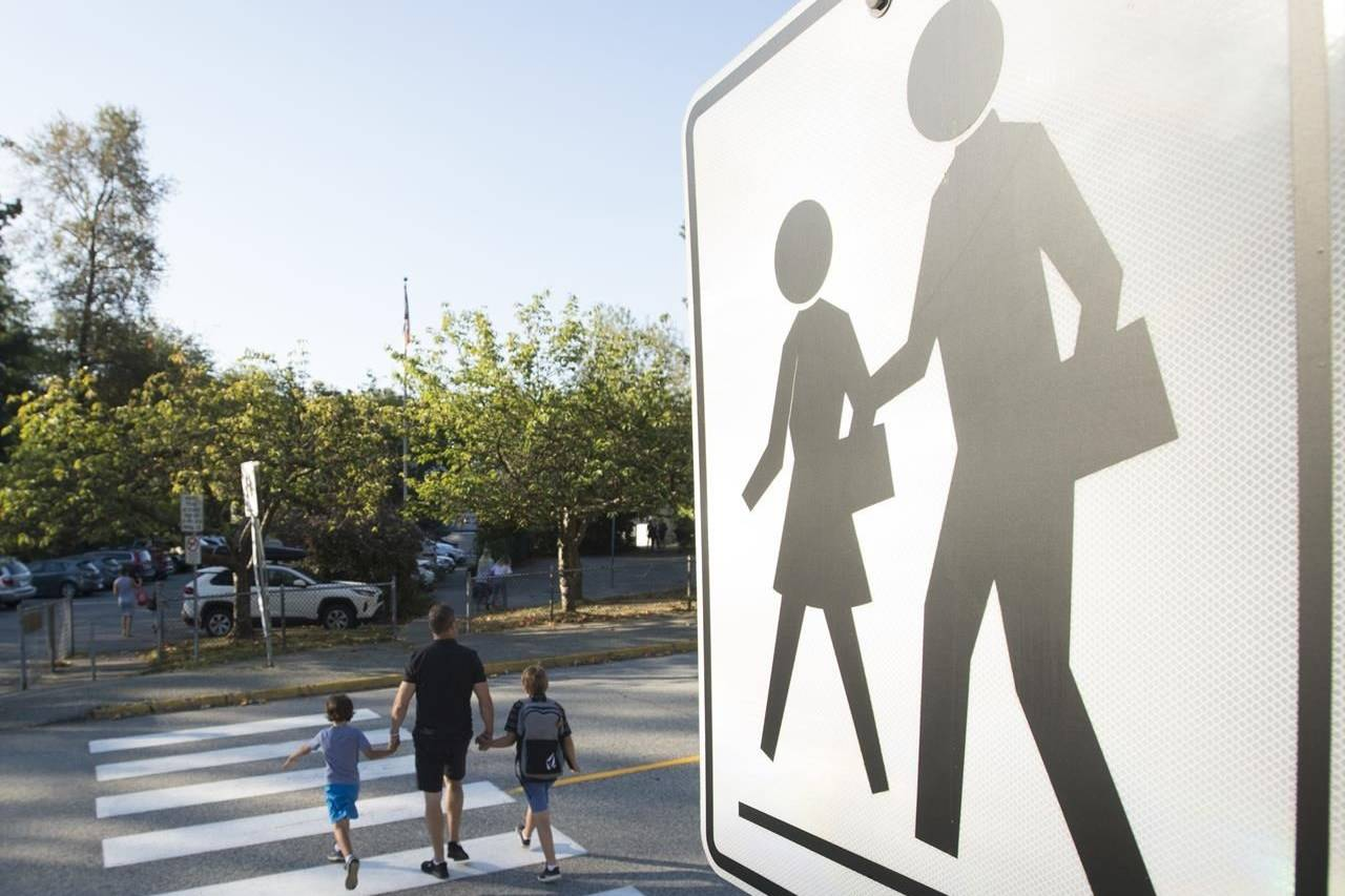 Children walk with their parents to Sherwood Park Elementary in North Vancouver for the first day back-to-school Thursday, September 10, 2020. Dr. Charlotte Waddell, a specialist in child and adolescent psychiatry, says she's expecting to see increases in the number of kids experiencing anxiety, depression, post-traumatic stress and other behavioural challenges as a result of the COVID-19 pandemic. THE CANADIAN PRESS/Jonathan Hayward