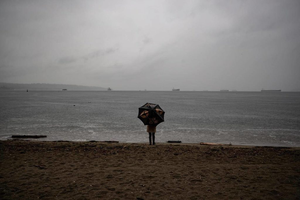 A person stands under an umbrella while looking out at English Bay as heavy rain falls, in Vancouver, B.C., Sunday, Oct. 11, 2020. THE CANADIAN PRESS/Darryl Dyck