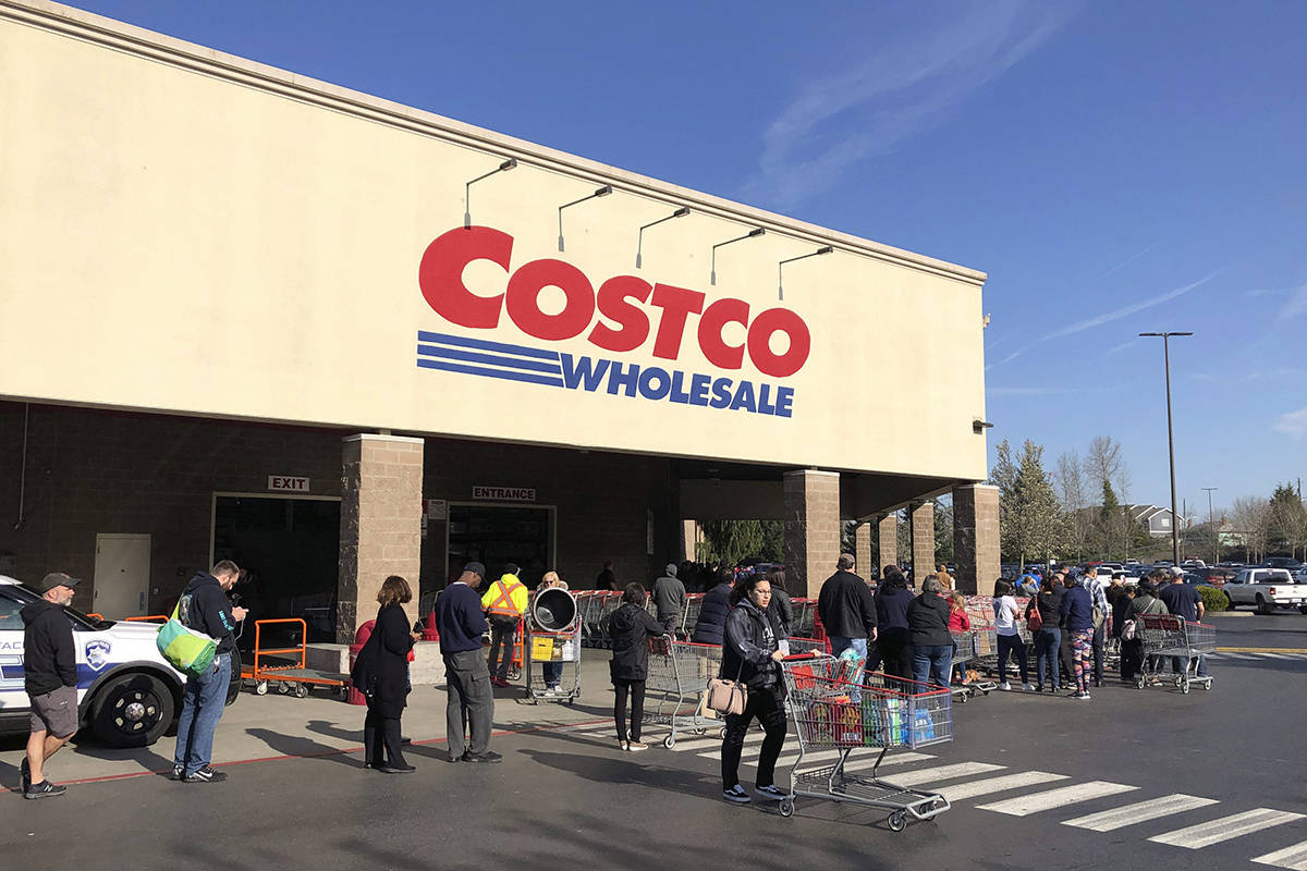 A shopper leaves as others line up to enter a Costco store, Friday, March 20, 2020, in Tacoma, Wash. Consumers continued to stock up on food and other items as officials urged people to stay at home to slow the spread of the new coronavirus. (AP Photo/Ted S. Warren)
