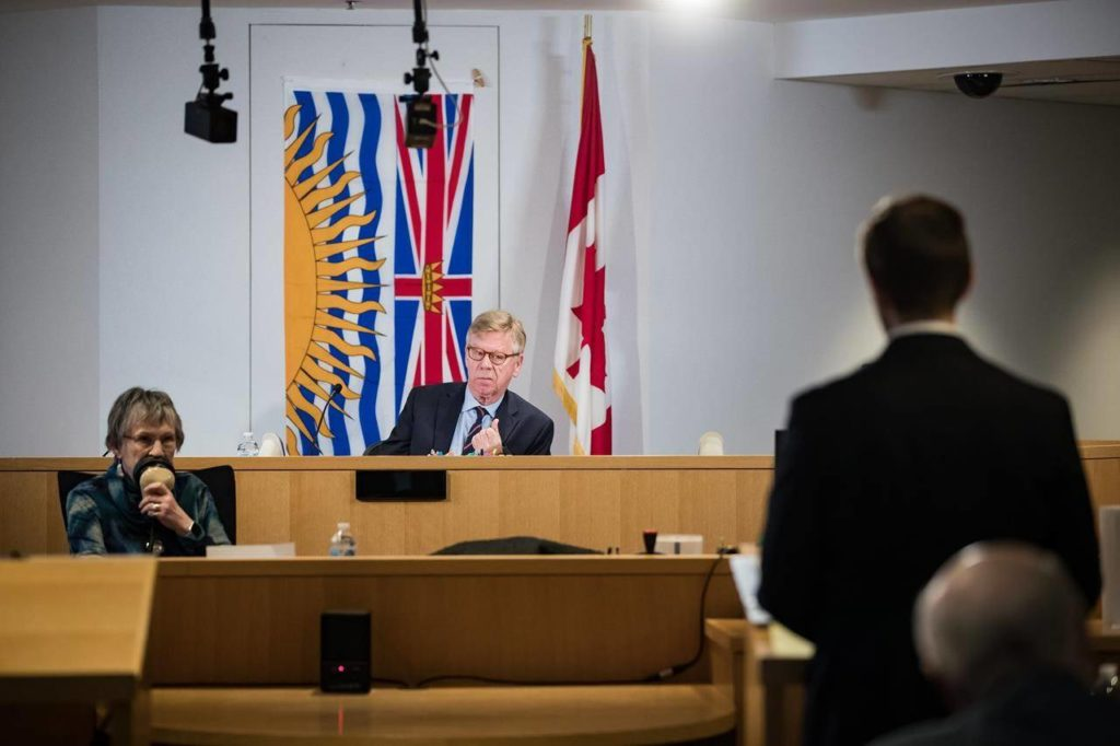 Commissioner Austin Cullen, back centre, listens to introductions before opening statements at the Cullen Commission of Inquiry into Money Laundering in British Columbia, in Vancouver, Monday, Feb. 24, 2020. A former British Columbia gaming policy official says the concerns about increasing amounts of suspicious cash and its possible links to money laundering at casinos started rising as the province was preparing to host the 2010 Winter Olympics. THE CANADIAN PRESS/Darryl Dyck