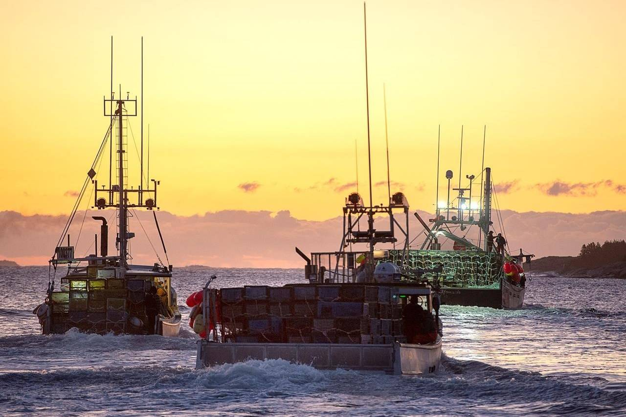 Fishing boats, loaded with traps, head from port as the lobster season on Nova Scotia's South Shore begins, in West Dover, N.S., Tuesday, Nov. 26, 2019. RCMP say a 74-year-old man faces charges in connection with a violent clash last month at a lobster pound in southwestern Nova Scotia. THE CANADIAN PRESS/Andrew Vaughan