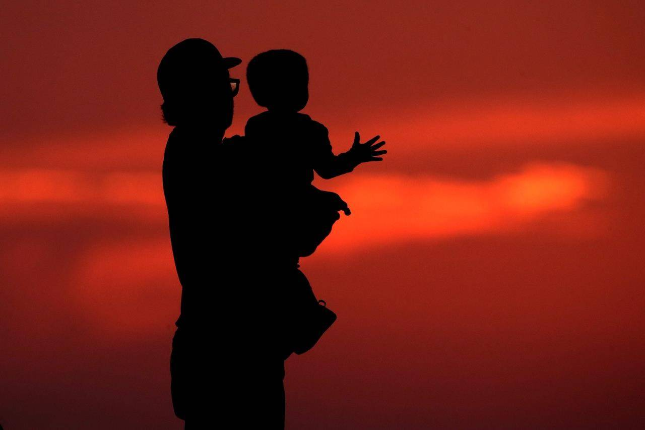 A man and his son are silhouetted against the sky as they watch the sunset from a park in Kansas City, Mo., Friday, June 26, 2020. A new survey shows caregivers for kids with autism, report their children's anxiety, routines and sleep quality have worsened in the fallout of the COVID-19 pandemic, along with parents' own wellbeing. THE CANADIAN PRESS/AP, Charlie Riedel
