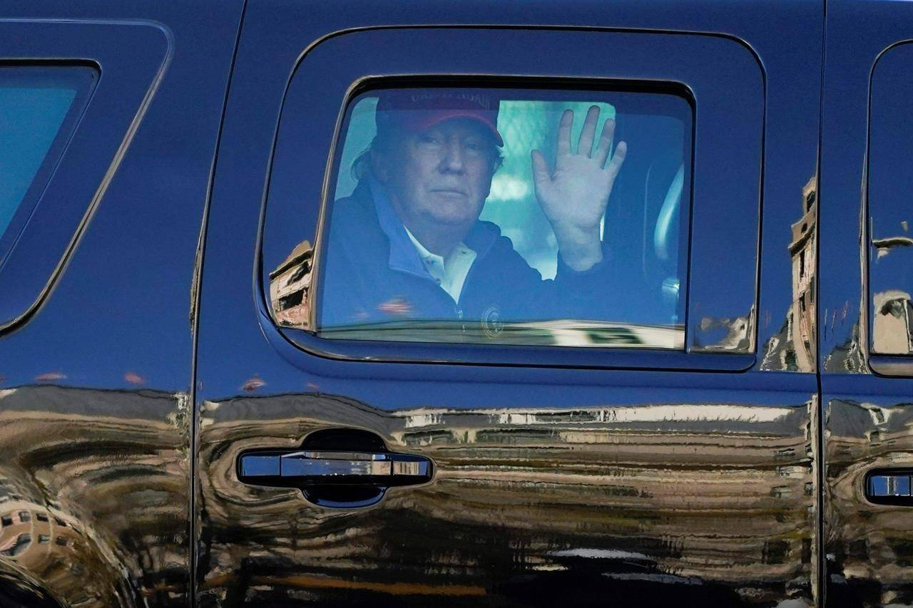 President Donald Trump waves to supporters from his motorcade as people gather for a march Saturday, Nov. 14, 2020, in Washington. (AP Photo/Julio Cortez)