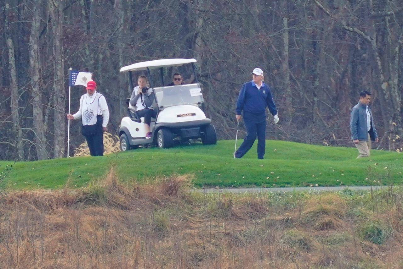 President Donald Trump, center, plays golf at Trump National Golf Club in Sterling, Va., as seen from the other side of the Potomac River in Darnestown, Md., Sunday, Nov. 15, 2020. (AP Photo/Manuel Balce Ceneta)