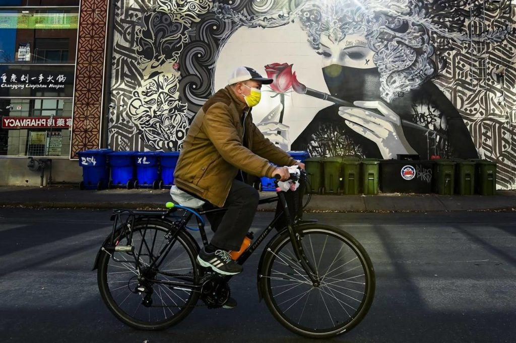 A man wearing a protective mask rides his bicycle past a face mask mural during the COVID-19 pandemic in Toronto on November 12, 2020. THE CANADIAN PRESS/Nathan Denette