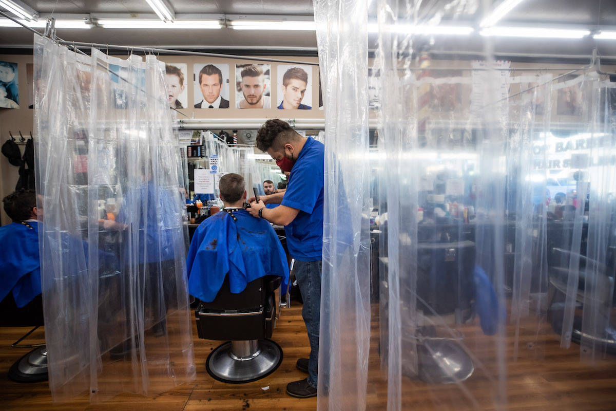 Fady Danial cuts Robert Bruce's hair at a barbershop that has erected plastic shower curtains as a measure to help curb the spread of COVID-19, in Burnaby, B.C., Nov. 7, 2020. THE CANADIAN PRESS/Darryl Dyck