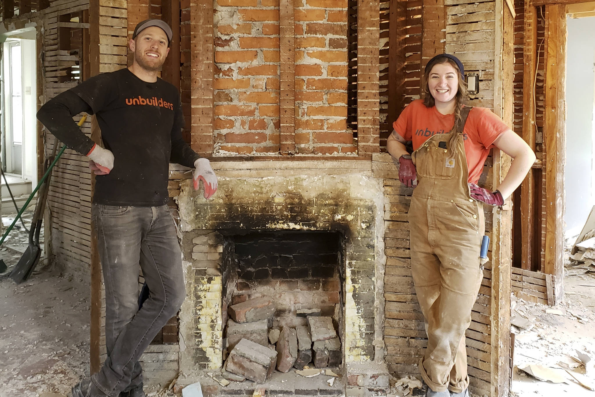Unbuilders owner Adam Corneil with employee Erin Watkins in front of a deconstructed hearth. Unbuilders crews carefully deconstruct old homes to rescue as many reusable materials as possible, including old-growth timber. (Unbuilders photo)