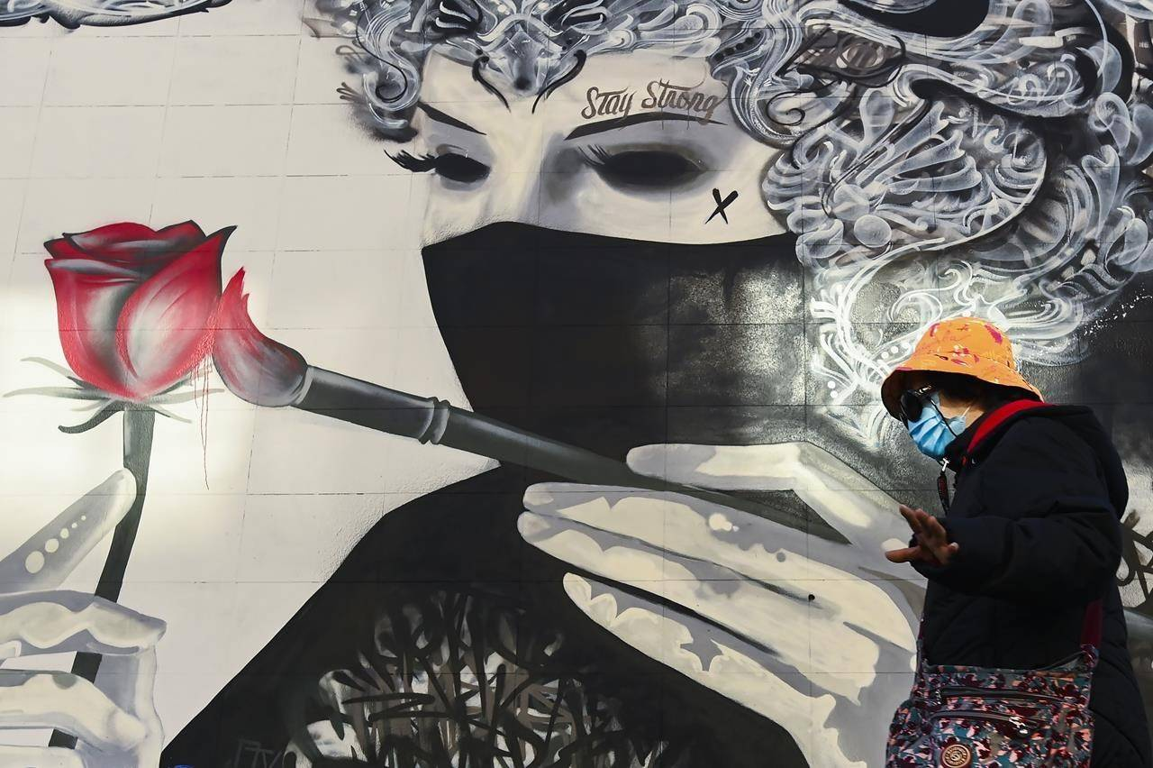 A woman wearing a protective mask walks past a face mask mural during the COVID-19 pandemic in Toronto on Thursday, November 12, 2020. THE CANADIAN PRESS/Nathan Denette