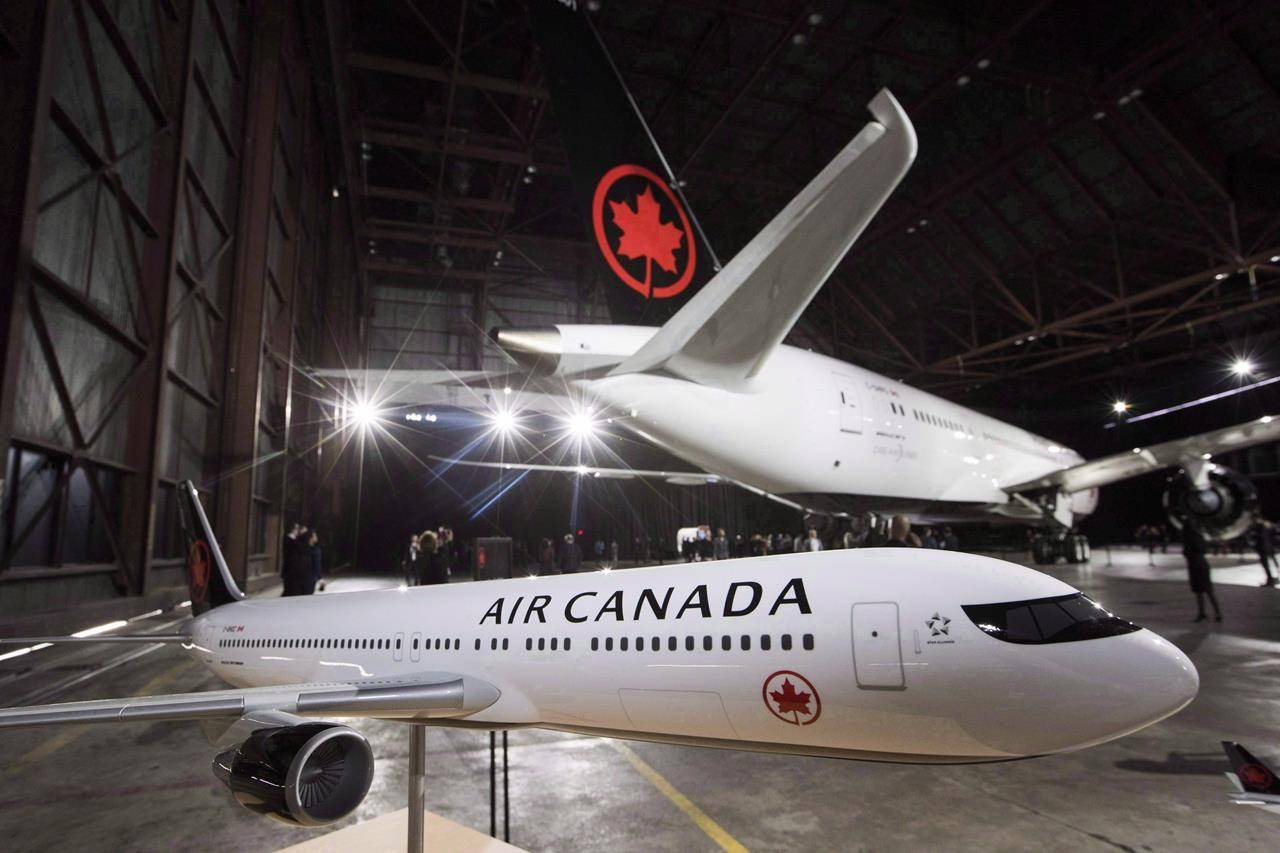 A model airplane is seen in front of the newly-revealed Air Canada Boeing 787-8 Dreamliner aircraft at a hangar at the Toronto Pearson International Airport in Mississauga, Ont., Thursday, February 9, 2017. Air Canada's three Aeroplan credit card partners are updating the features of the airline's main customer loyalty program for travellers.THE CANADIAN PRESS/Mark Blinch