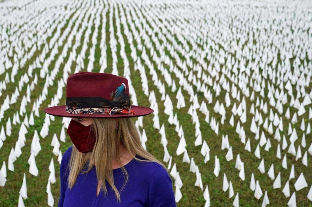 """Artist Suzanne Brennan Firstenberg stands among thousands of white flags planted in remembrance of Americans who have died of COVID-19, Tuesday, Oct. 27, 2020, near Robert F. Kennedy Memorial Stadium in Washington. Firstenberg's temporary art installation is called """"In America, How Could This Happen."""" THE CANADIAN PRESS/AP, Patrick Semansky"""