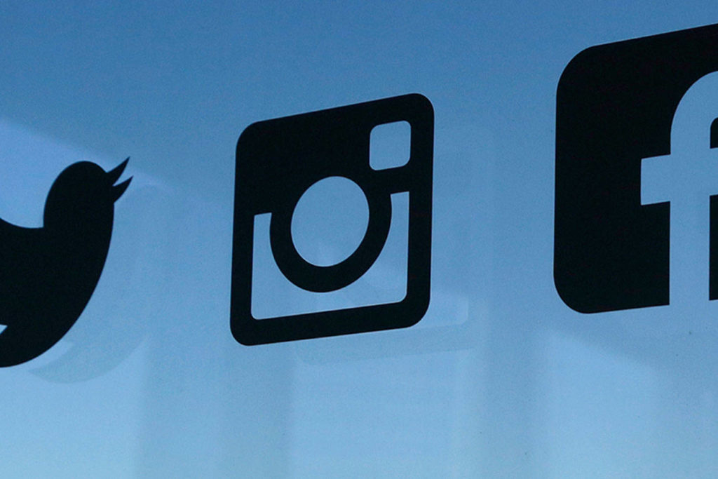 Icons for the Twitter, Instagram, Facebook and Pinterest social media platforms are displayed on a window in New York. (AP Photo/Mark Lennihan, File)