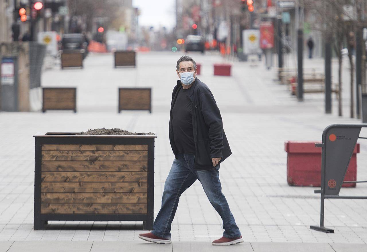 A man wears a face mask as he walks along a street in Montreal, Sunday, November 15, 2020.THE CANADIAN PRESS/Graham Hughes