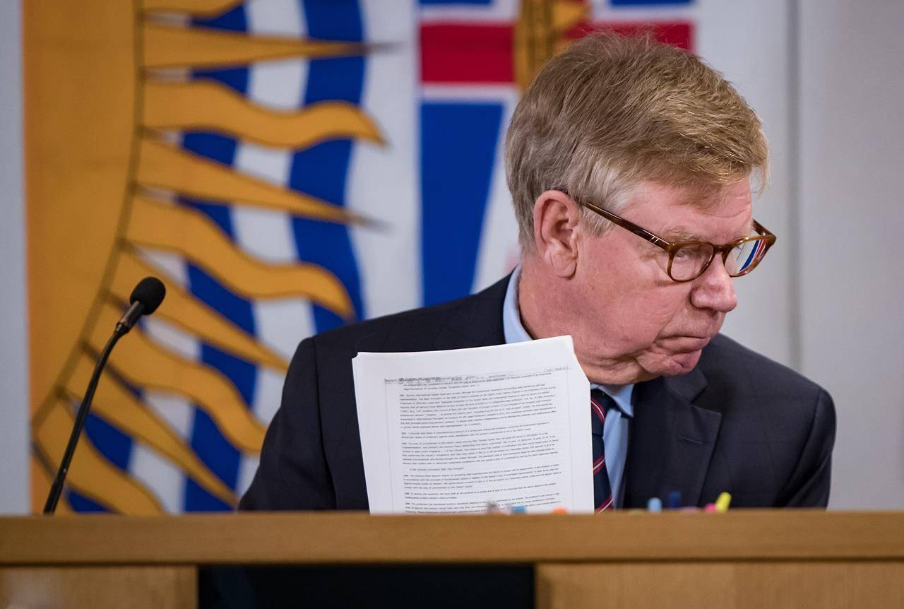 Commissioner Austin Cullen looks at documents before opening statements at the Cullen Commission of Inquiry into Money Laundering in British Columbia, in Vancouver on February 24, 2020. (THE CANADIAN PRESS/Darryl Dyck)