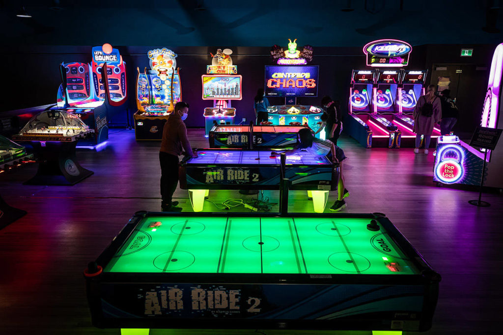 People wearing protective face masks play an air hockey game at Central City Fun Park on their opening weekend, in Surrey, B.C., on Sunday, June 7, 2020. THE CANADIAN PRESS/Darryl Dyck