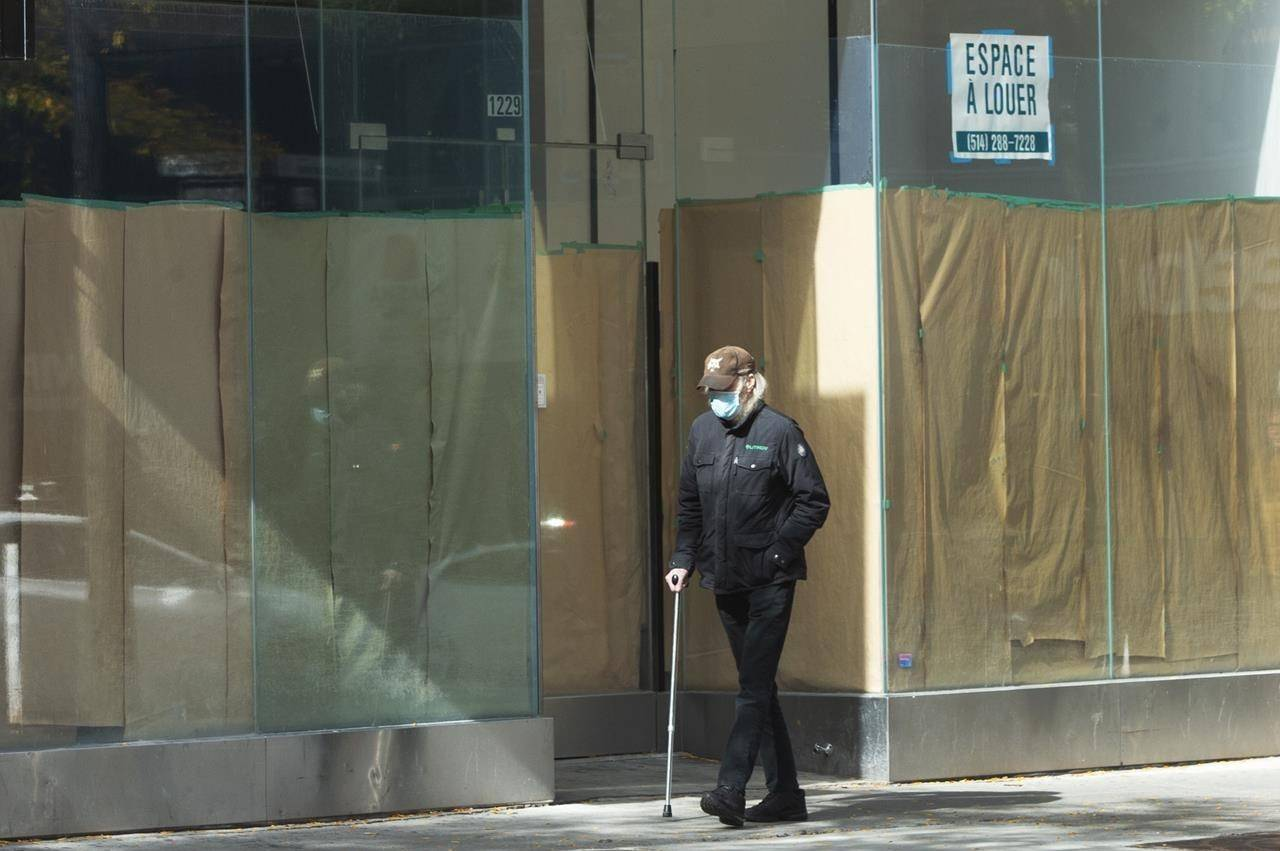 A pedestrian walks past a closed storefront on St. Catherine street as the COVID-19 pandemic continues to take its toll on local businesses, Thursday, Oct. 8, 2020 in Montreal. THE CANADIAN PRESS/Ryan Remiorz