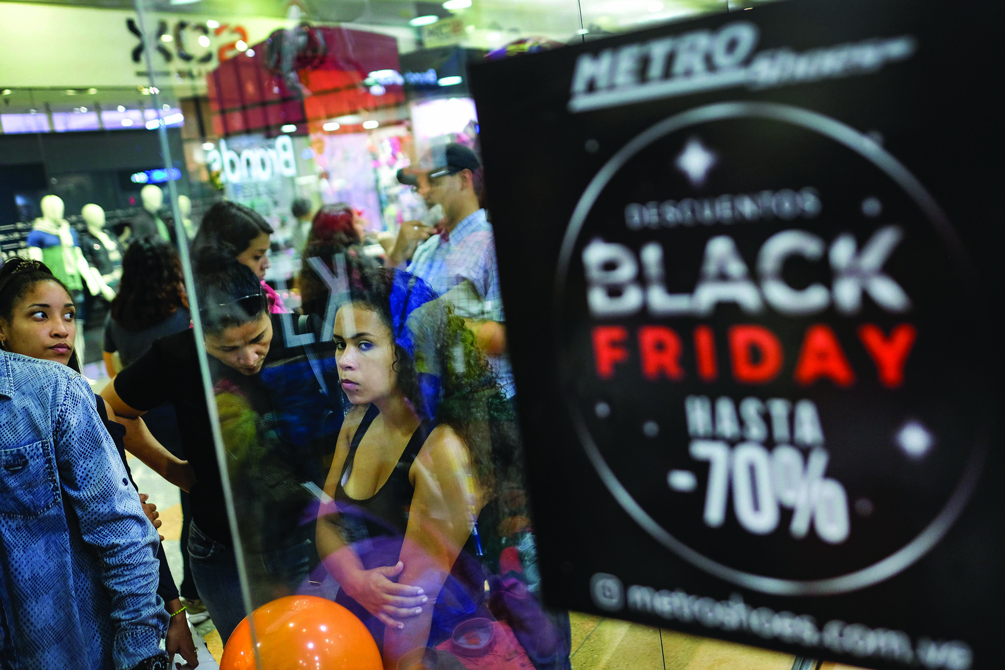 Shoppers stand near a sign promoting Black Friday sales at the Sambil shopping centre in Caracas, Venezuela, Friday, Nov. 29, 2019. This year, Black Friday is on Nov. 27, the same day as Buy Nothing Day. (AP Photo/Matias Delacroix)