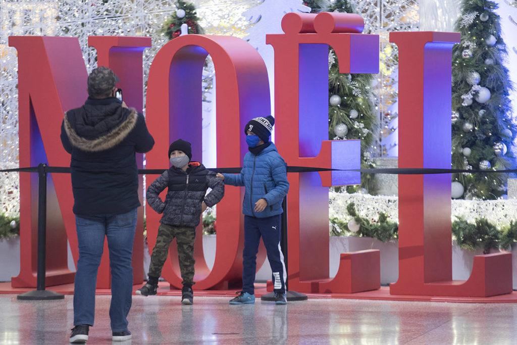 People pose next to a Christmas display in Montreal, Sunday, November 22, 2020, as the COVID-19 pandemic continues in Canada and around the world. THE CANADIAN PRESS/Graham Hughes