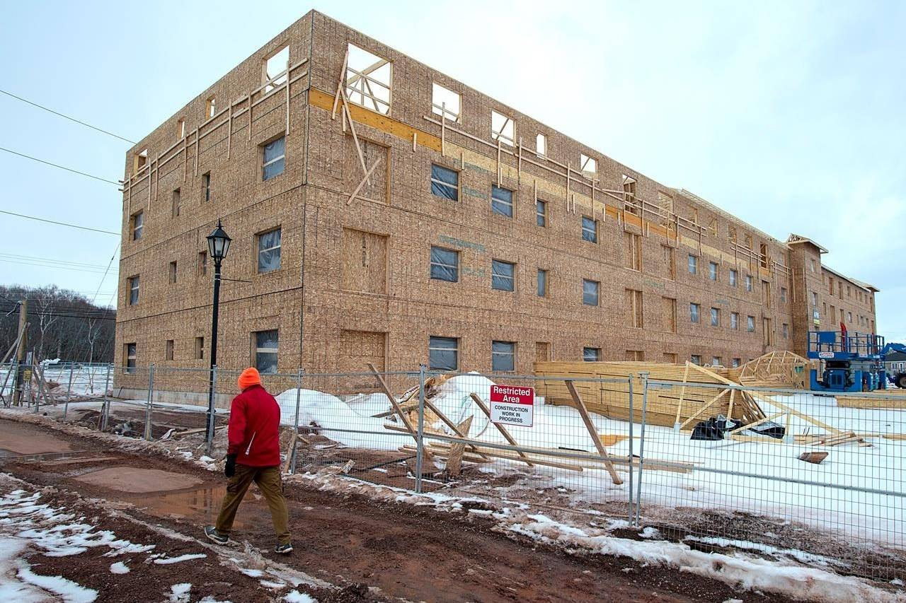 A man walks past an affordable housing complex, being constructed in Charlottetown's Hillsborough Park area, on Saturday, February 29, 2020. Seven provinces have signed on to a federal rent assistance program created as part of the national housing strategy, three more than the Liberals have announced, newly released documents show. THE CANADIAN PRESS/Andrew Vaughan