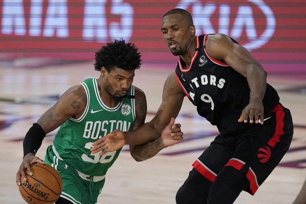 Boston Celtics' Marcus Smart (36) moves around Toronto Raptors' Serge Ibaka (9) in the second half of an NBA conference semifinal playoff basketball game Thursday, Sept 3, 2020, in Lake Buena Vista Fla. (AP Photo/Mark J. Terrill)