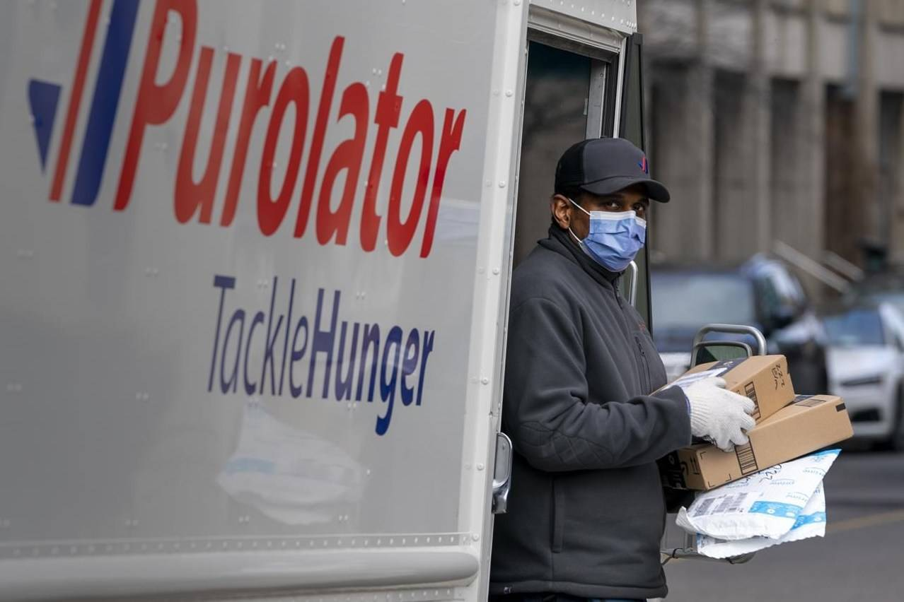A Purolator driver wears a mask as he makes deliveries in Toronto on March 24, 2020. With online sales set to hit record highs this year, Statistics Canada says that wholesalers, rather than retailers, have benefited most from the trend toward online shopping. Statistics Canada says $85 billion of Canada's $305 billion in online sales last year went to wholesalers, while transportation and warehousing companies got $60 billion, manufacturing was worth $38 billion, and retailers grossed $22 billion.THE CANADIAN PRESS/Frank Gunn