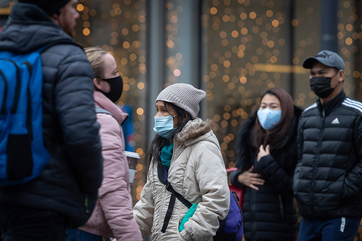People wearing face masks to help curb the spread of COVID-19 cross a street in downtown Vancouver, on Sunday, November 22, 2020. The use of masks is mandatory in indoor public and retail spaces in the province. THE CANADIAN PRESS/Darryl Dyck
