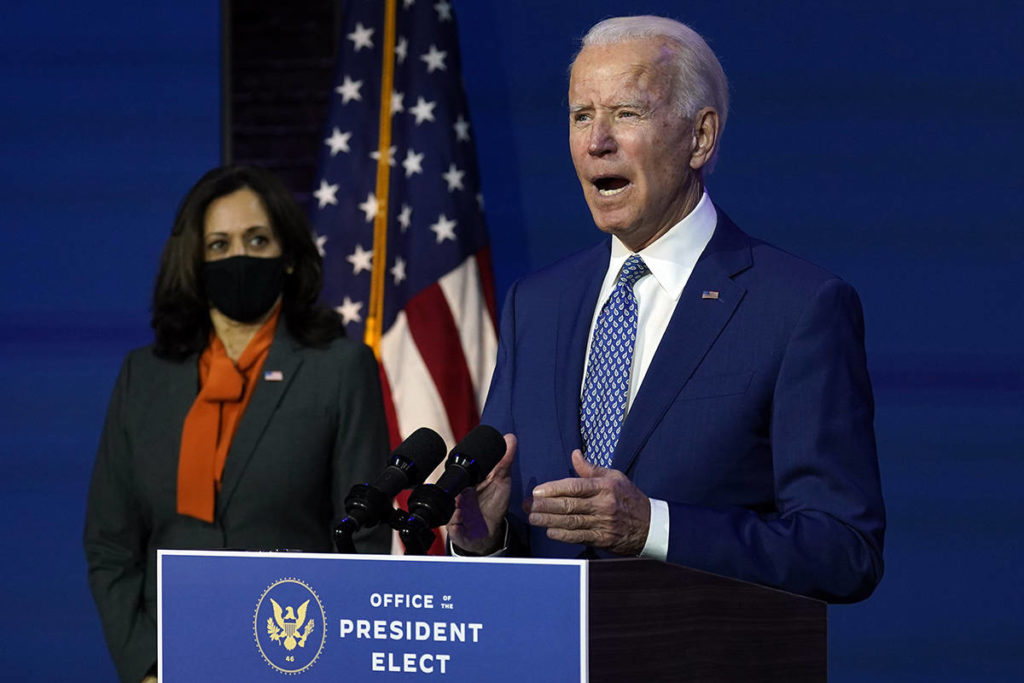 President-elect Joe Biden speaks Monday, Nov. 9, 2020, at The Queen theater in Wilmington, Del., as Vice President-elect Kamala Harris listens. (AP Photo/Carolyn Kaster)