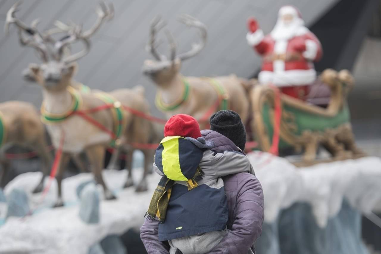 A man and child walk by a Santa Claus reindeer display on a street in Montreal, Sunday, November 22, 2020, as the COVID-19 pandemic continues in Canada and around the world. THE CANADIAN PRESS/Graham Hughes