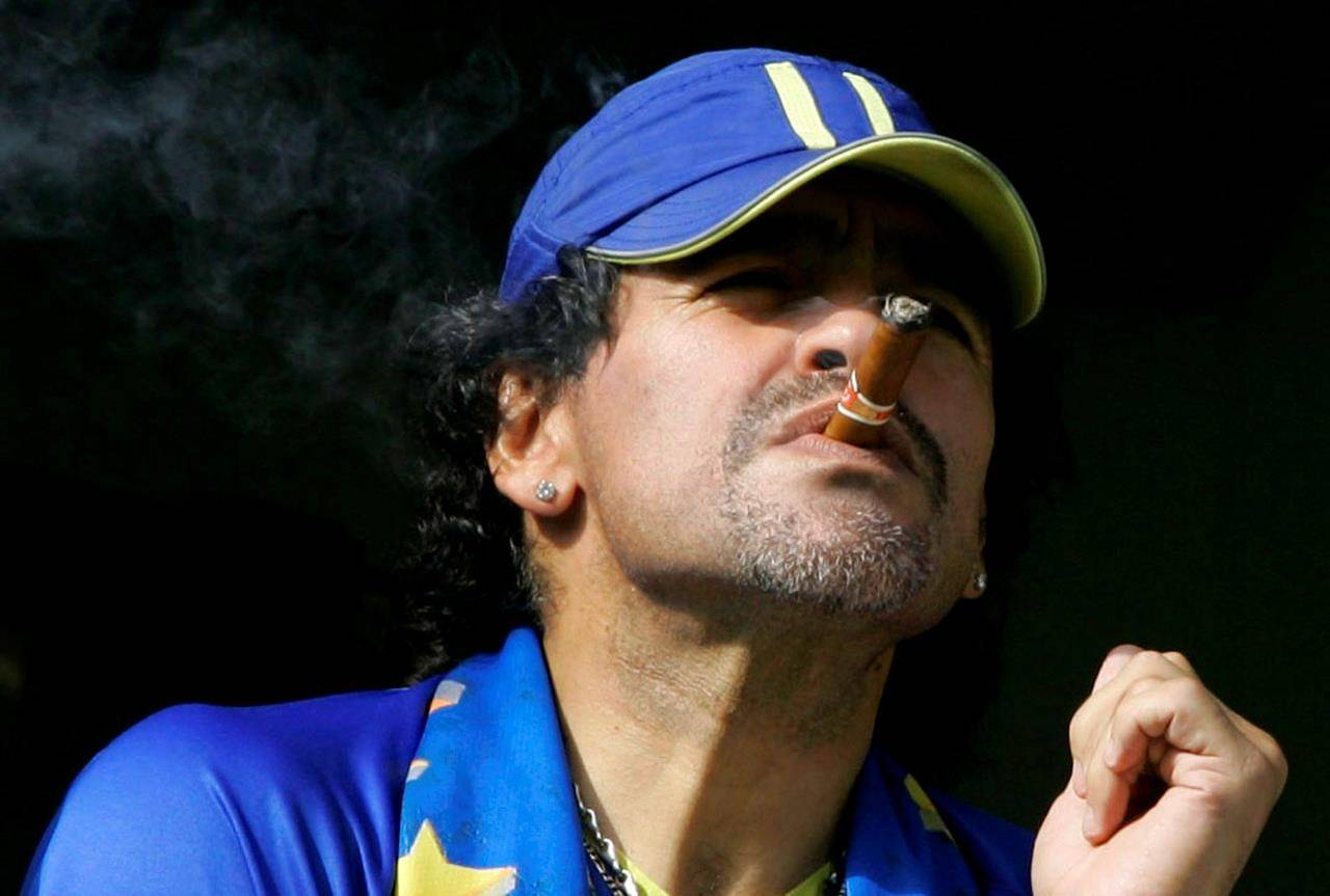 FILE - In this March 26, 2006 file photo, former soccer player Diego Maradona smokes a cigar as he watches Argentina's first division soccer match between Boca Juniors and River Plate in Buenos Aires, Argentina. The Argentine soccer great who was among the best players ever and who led his country to the 1986 World Cup title before later struggling with cocaine use and obesity, died from a heart attack on Wednesday, Nov. 25, 2020, at his home in Buenos Aires. He was 60. (AP Photo/Natacha Pisarenko, File)