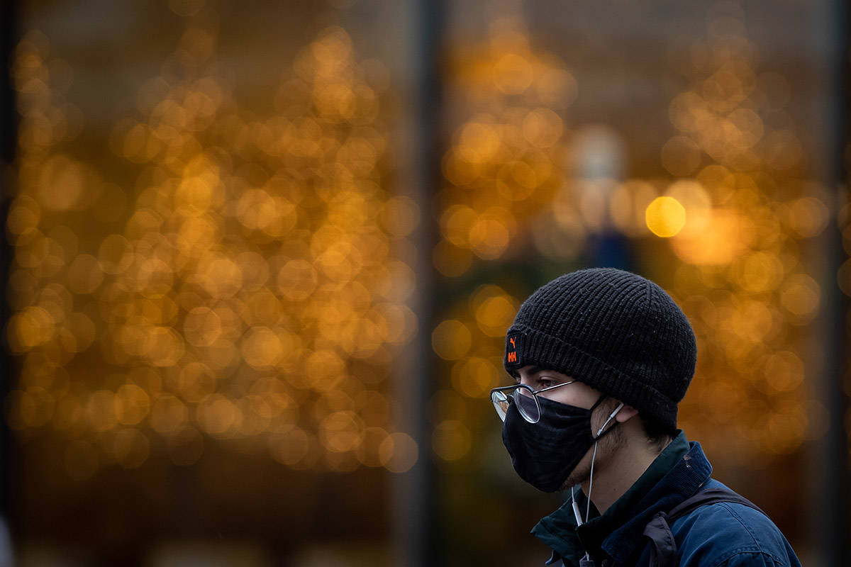 A man wearing a face mask to help curb the spread of COVID-19 walks in downtown Vancouver, B.C., Sunday, Nov. 22, 2020. The use of masks is mandatory in indoor public and retail spaces in the province. THE CANADIAN PRESS/Darryl Dyck