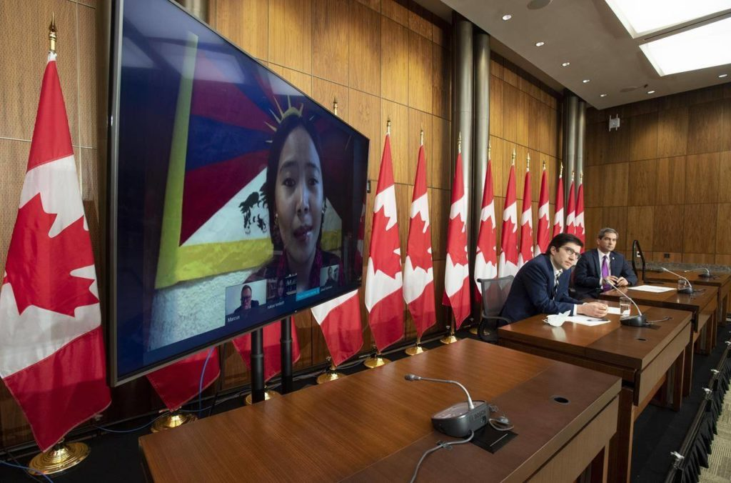 Conservative MP Garnett Genuis and Pierre Paul-Hus listen to Chemi Lhamo during a news conference in Ottawa, Thursday, Nov. 26, 2020. Canadians who say they have been victims of threats and intimidation by Chinese, Iranian and Russian foreign agents are saying that domestic police forces are ill-equipped to deal with their concerns. THE CANADIAN PRESS/Adrian Wyld