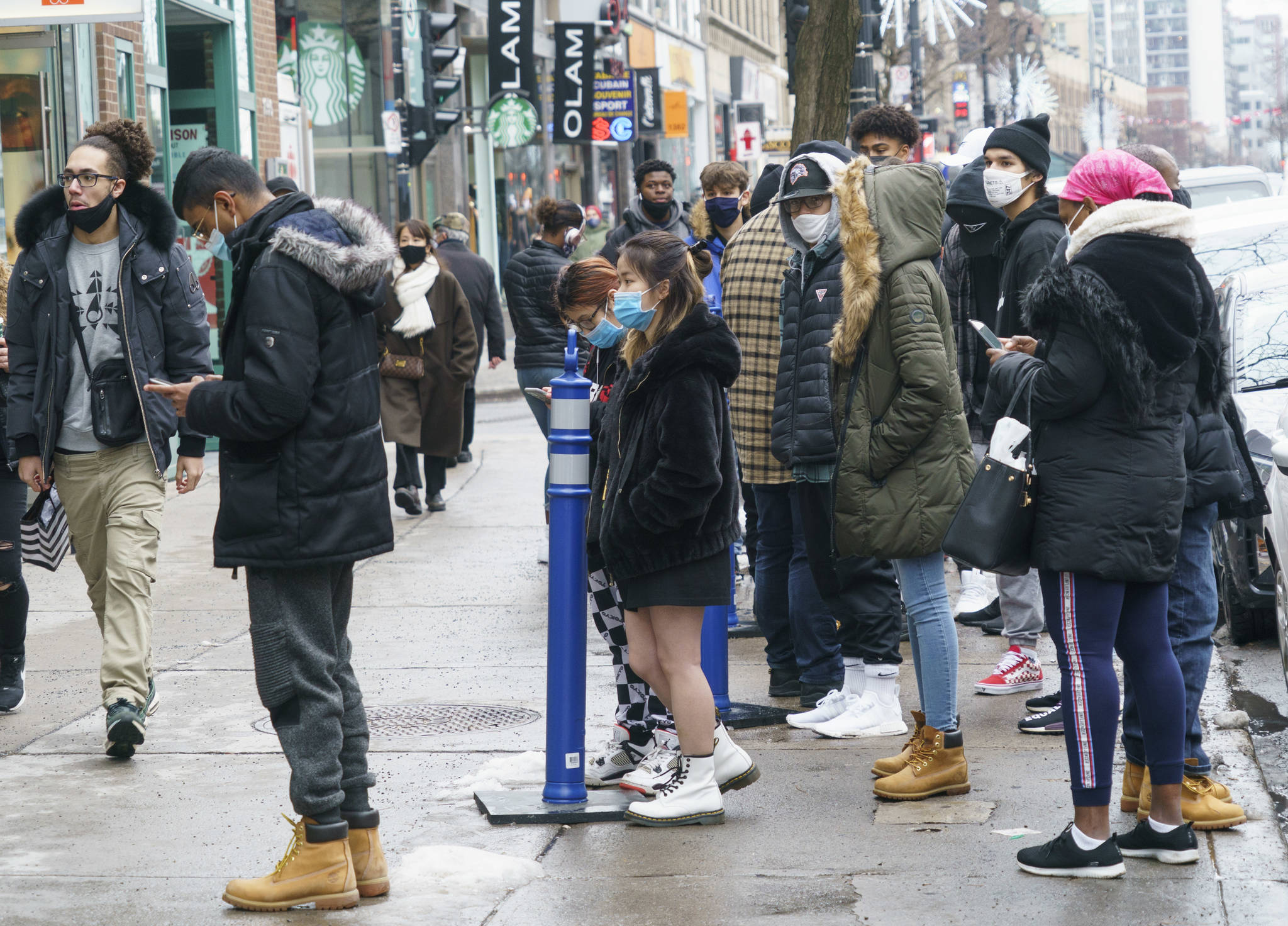 Shoppers line up in front of a shop on Montreal's Saint-Catherine Street in search of Black Friday deals in Montreal, Friday, Nov. 27, 2020. THE CANADIAN PRESS/Paul Chiasson