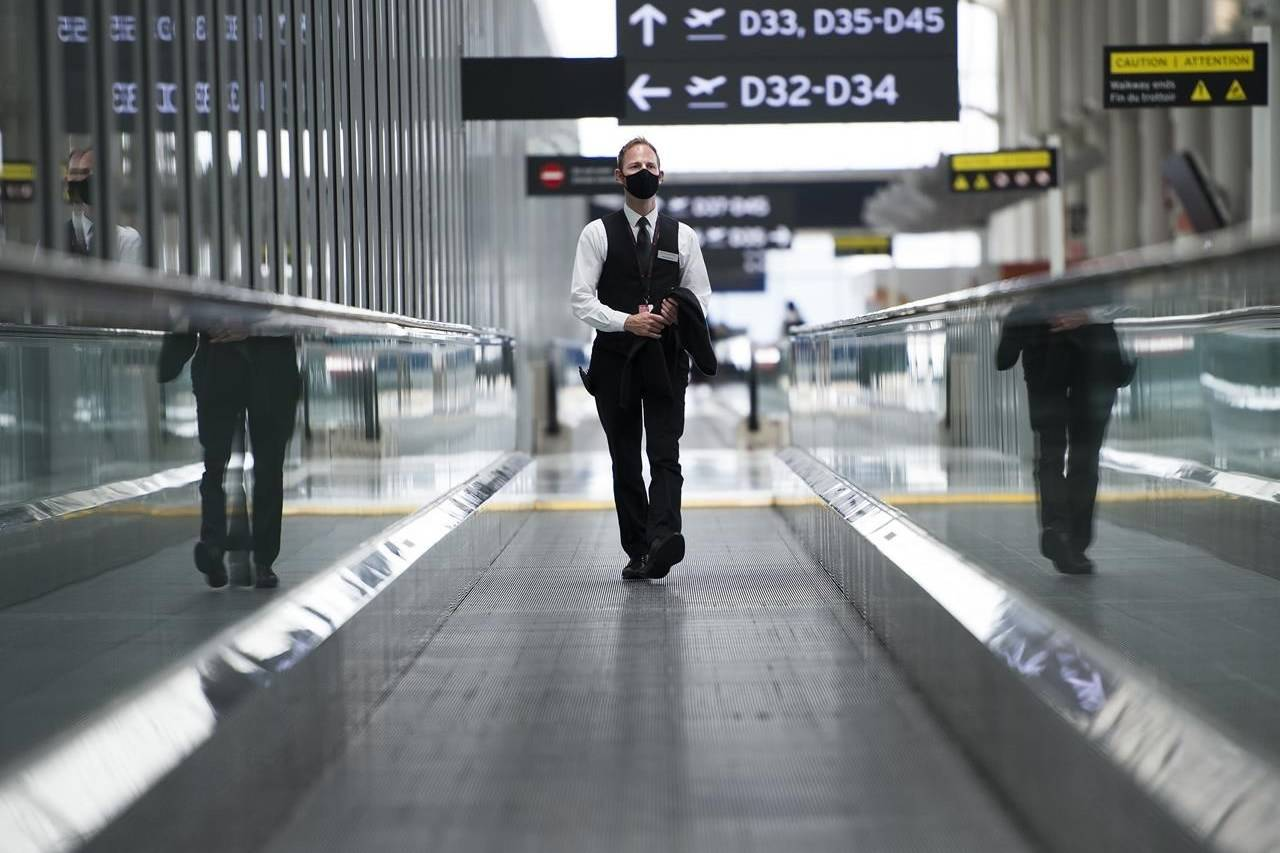 """A man rides a escalator wearing mandatory masks at Toronto's Pearson International Airport for a """"Healthy Airport"""" during the COVID-19 pandemic in Toronto, Tuesday, June 23, 2020. The Federal Court has punted consideration of airfare refunds, which customers say they are owed following hundreds of thousands of cancelled flights, to provincial courts. THE CANADIAN PRESS/Nathan Denette"""