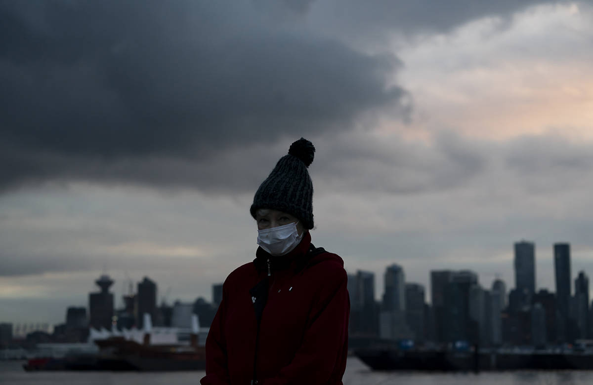 A woman wears a protective face covering to help prevent the spread of COVID-19 as she walks along the seawall in North Vancouver Wednesday, November 25, 2020.THE CANADIAN PRESS/Jonathan Hayward