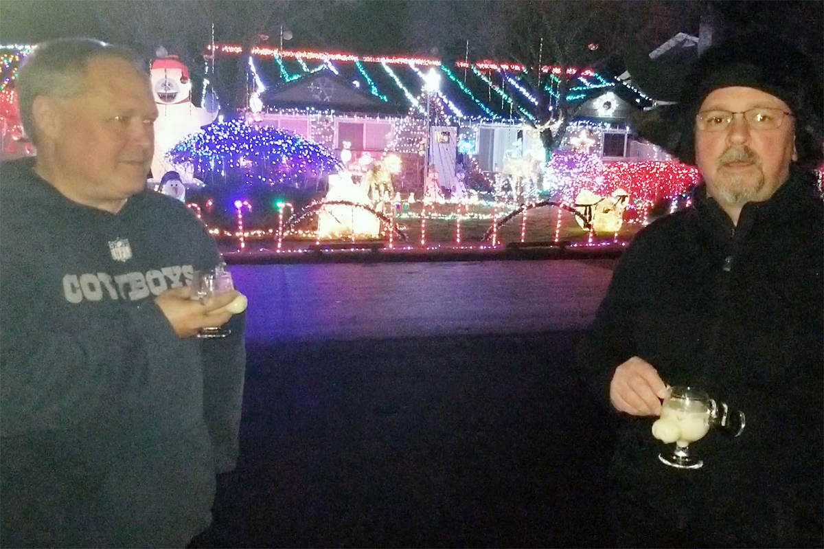 Neighbours Rob Baerg (L) and Ken Sherwood toasted the successful launch of their latest gigantic Christmas light display on their front lawns in the 20600 block of 44A Avenue on Sunday, Nov, 29, 2020 (Dan Ferguson/Langley Advance Times)
