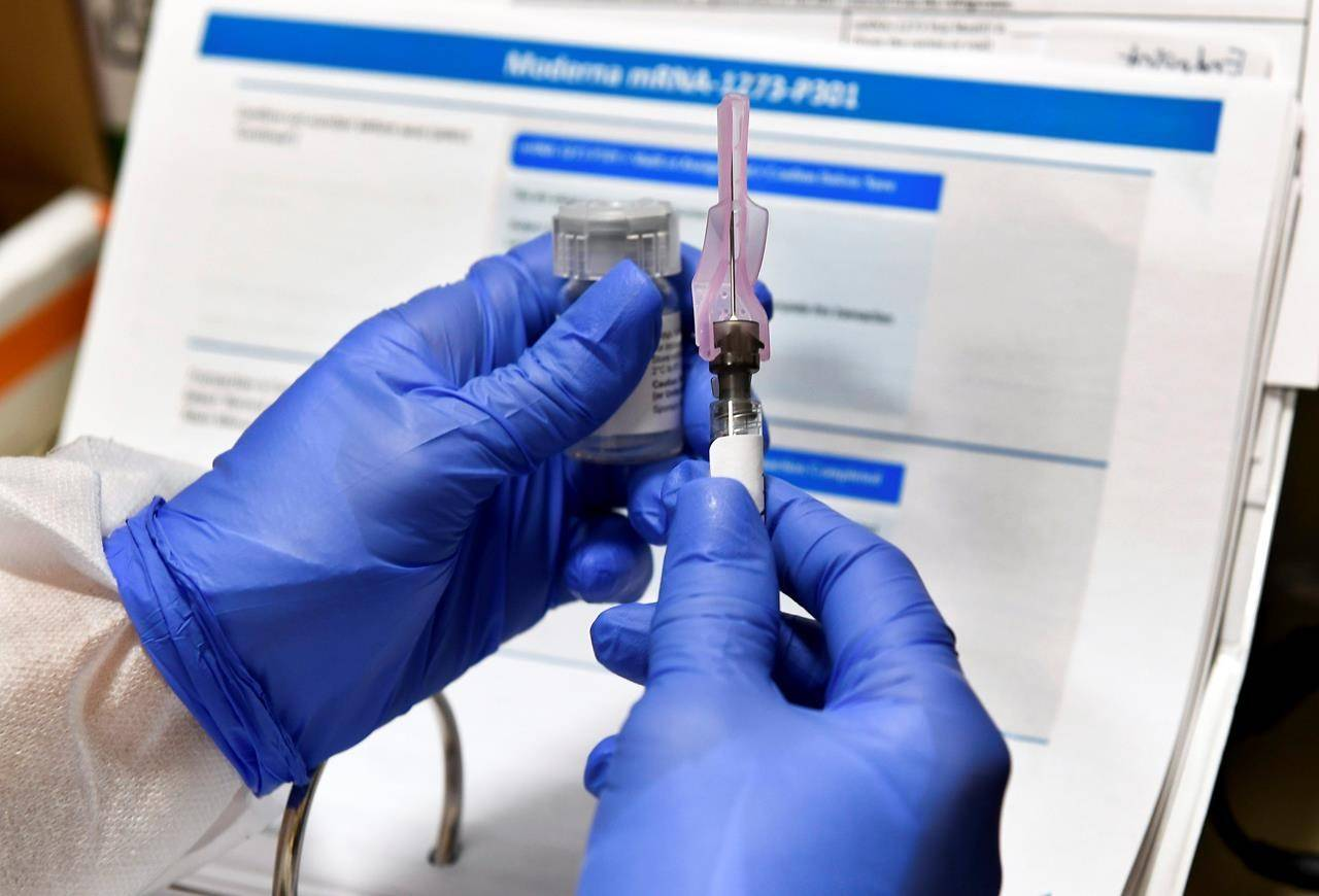 FILE - In this July 27, 2020, file photo, nurse Kathe Olmstead prepares a shot that is part of a possible COVID-19 vaccine, developed by the National Institutes of Health and Moderna Inc., in Binghamton, N.Y. Moderna Inc. says it will ask U.S. and European regulators to allow emergency use of its COVID-19 vaccine as new study results confirm the shots offer strong protection. (AP Photo/Hans Pennink, File)