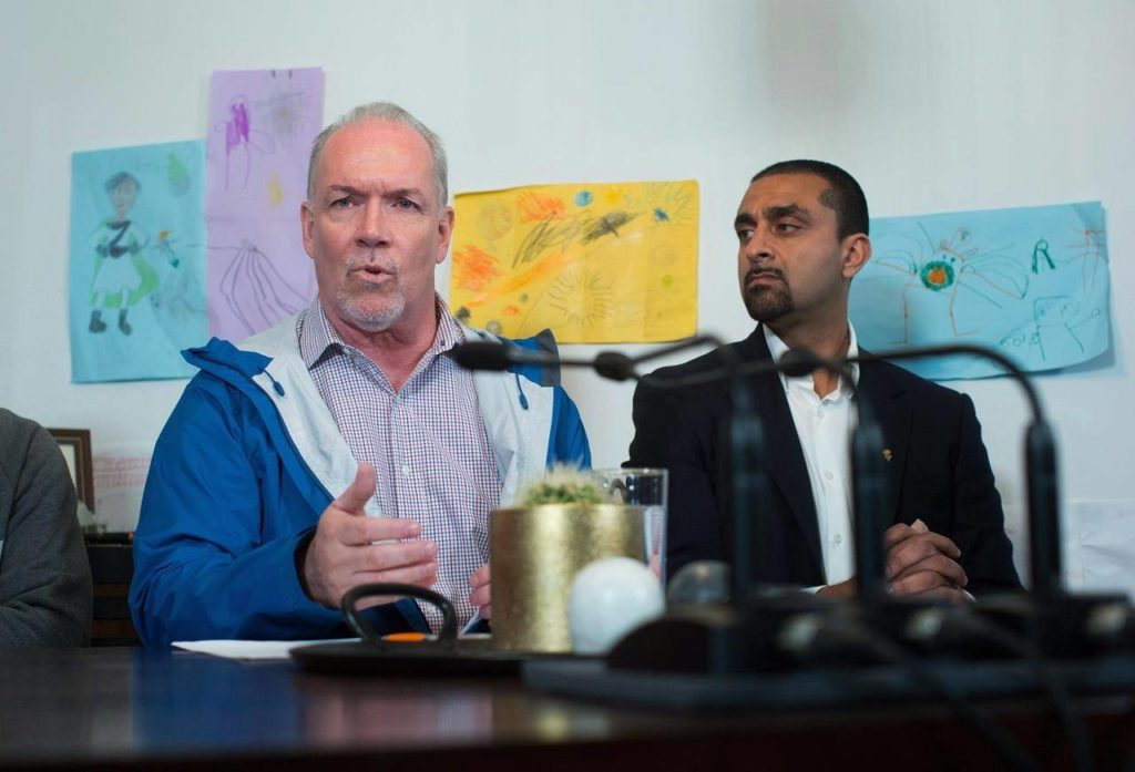 NDP Leader John Horgan, left, speaks as local candidate Ravi Kahlon listens during a campaign stop at Kahlon's home in North Delta, B.C., on April 18, 2017. THE CANADIAN PRESS/Darryl Dyck
