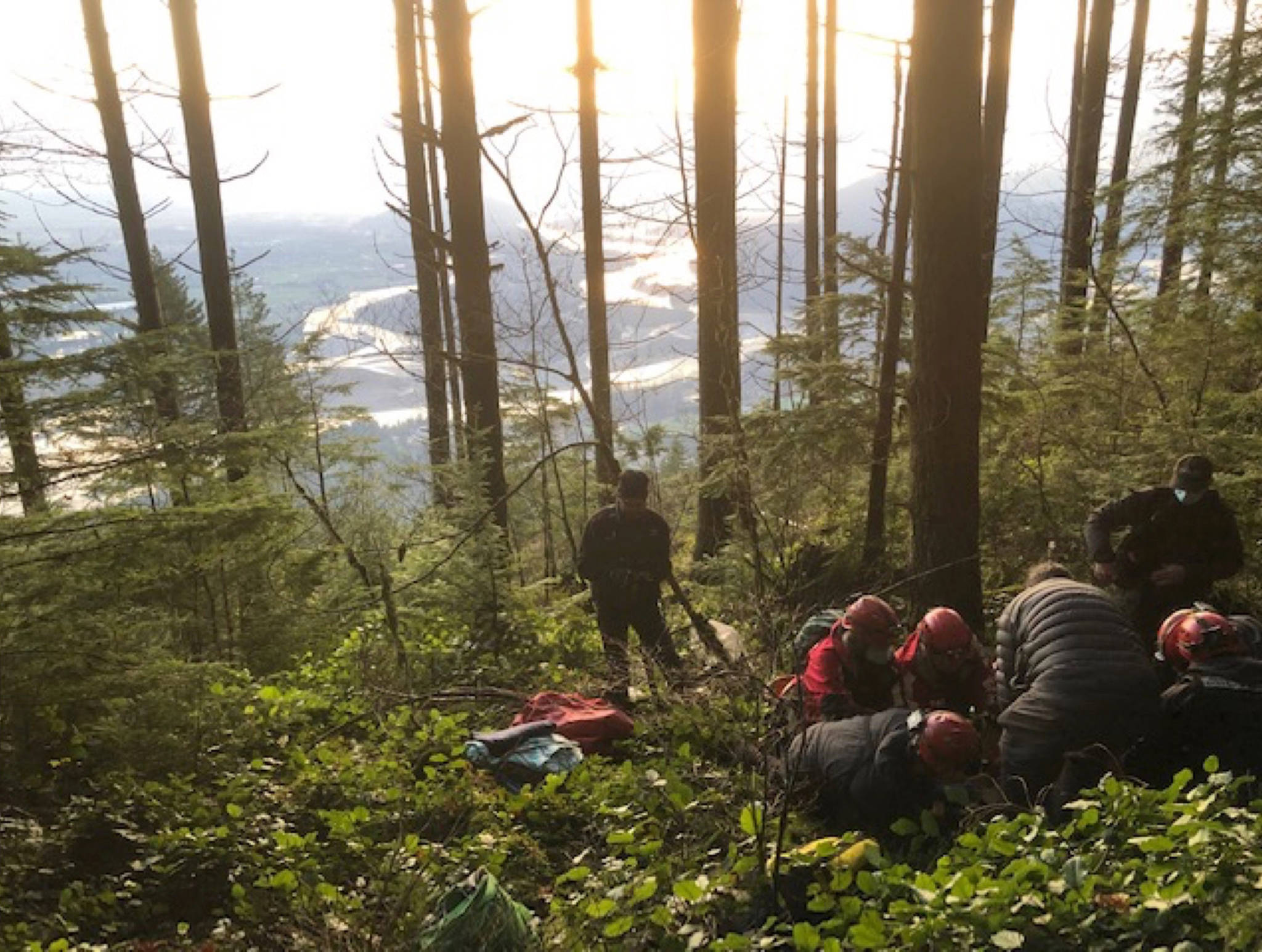 Kent-Harrison Search and Rescue members work quickly to prepare a badly injured paraglider pilot for transport following a harrowing treetop rescue this past weekend. (Contributed Photo/Dave Harder)
