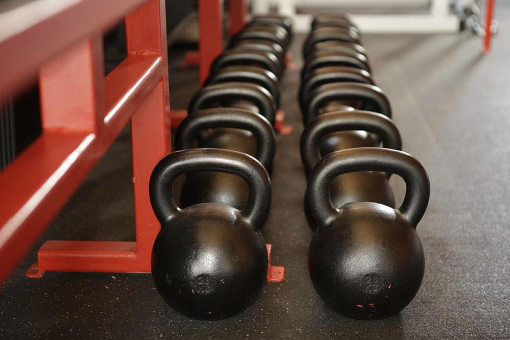 Kettle bells sit aligned in an indoor fitness studio. (PIxabay.com)