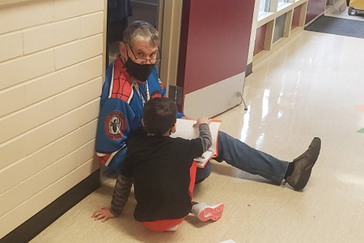 Troy Tardiff reads with a student in the hallways at Shortreed Elementary. (Shortreed Community Elementary/Special to the Langley Advance Times)