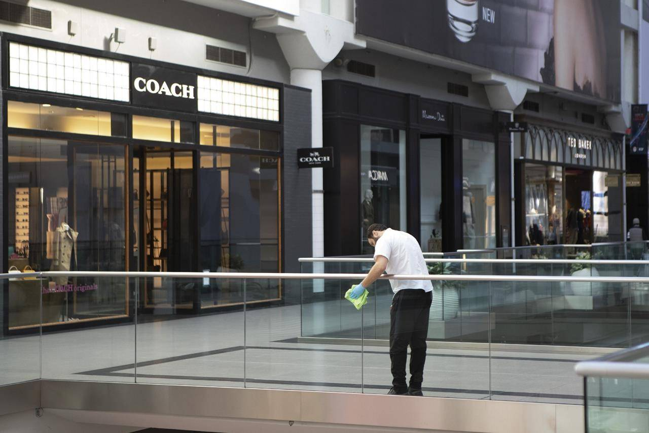 A cleaner wipes a glass panel at Toronto's Eaton Centre Shopping mall on Saturday, March 21, 2020. The national statistics office will say this morning how much the domestic economy bounced back in the third quarter of the year. The Canadian economy suffered its worst three-month stretch on record in the second quarter as the economy came to a near halt in April before starting to recover in May and June. THE CANADIAN PRESS/Chris Young