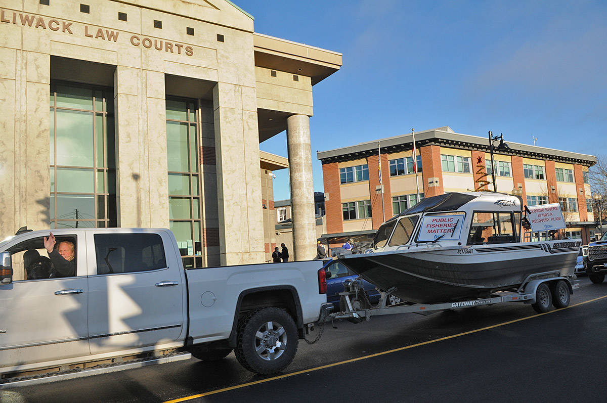 A convoy of seven pickup trucks, six of which were hauling boats, makes its way around the Chilliwack Law Courts on Dec. 1, 2020. (Jenna Hauck/ Chilliwack Progress)
