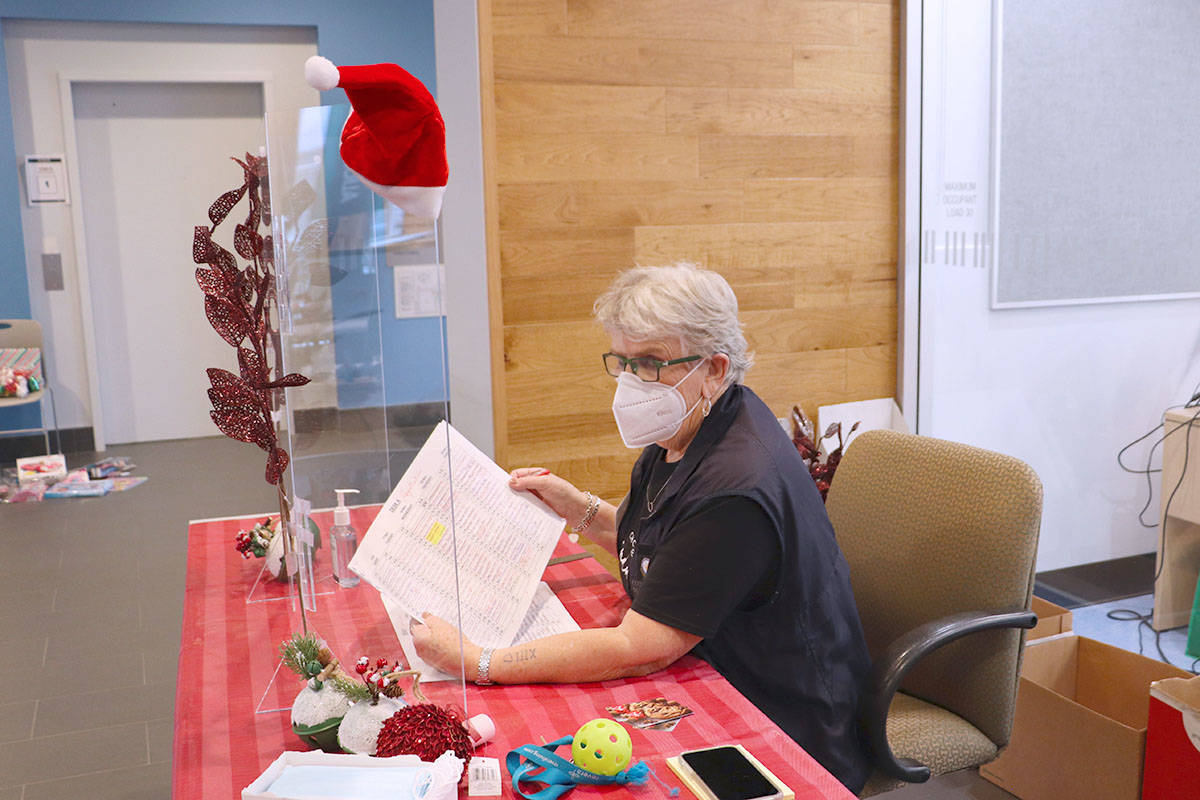 Velma MacAllister, coordinator of the Langley Christmas Bureau, sits behind a Plexi-glass barrier to check-in clients visiting the charity's temporary location at Timms Community Centre at Langley City hall during the 2020 holiday season. (Joti Grewal/Langley Advance Times)