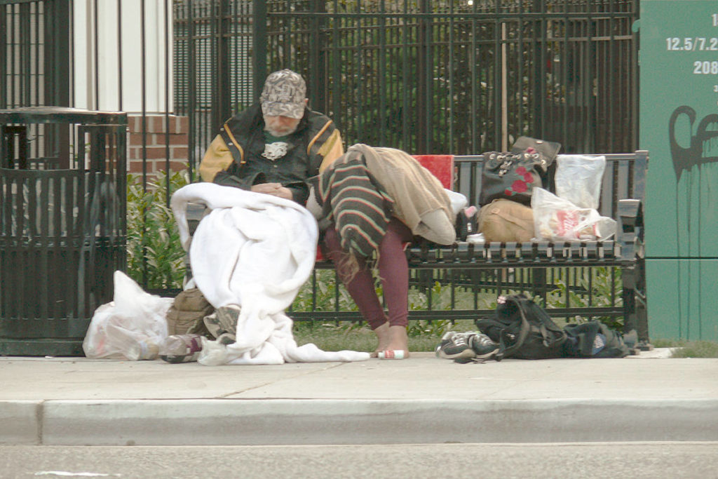 A homeless couple nap on a Langley City bench in 2018. According to new stats, the number of homeless who live outdoors is on the rise in the City and Township. (Langley Advance Times file)