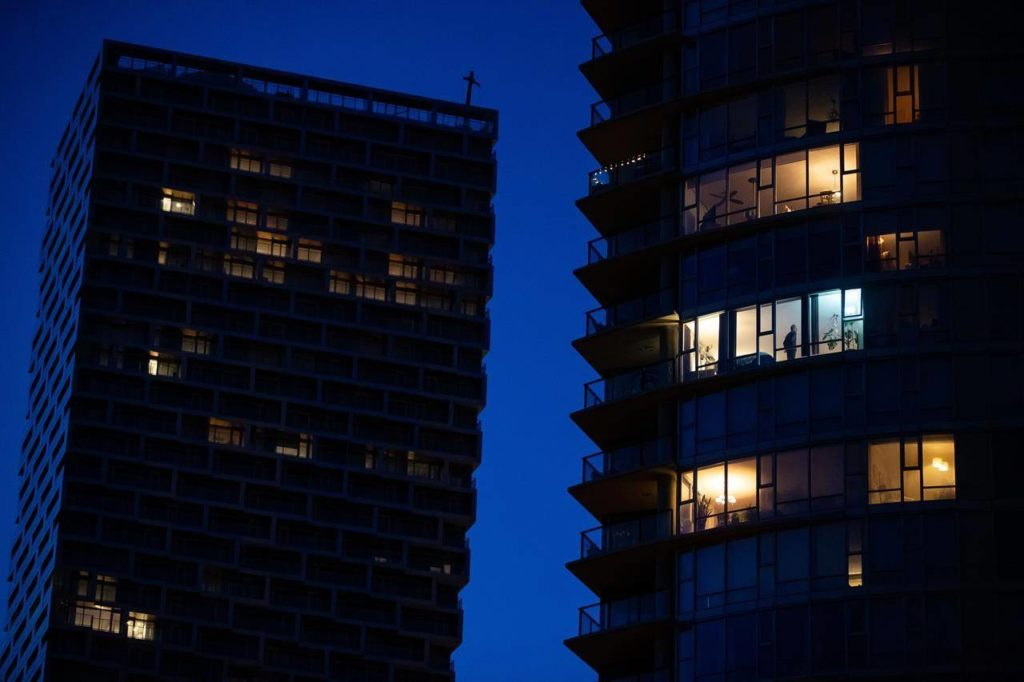 A man stands in the window of an upper floor condo in Vancouver on March 24, 2020. THE CANADIAN PRESS/Darryl Dyck
